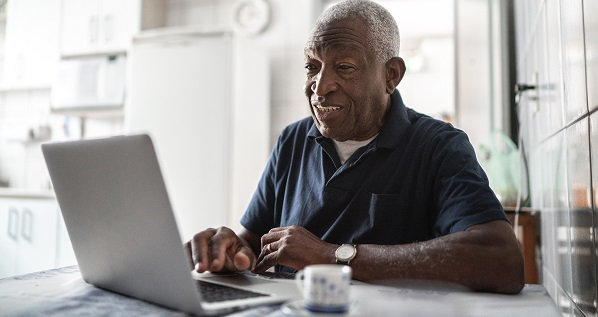 Senior man working at laptop at home